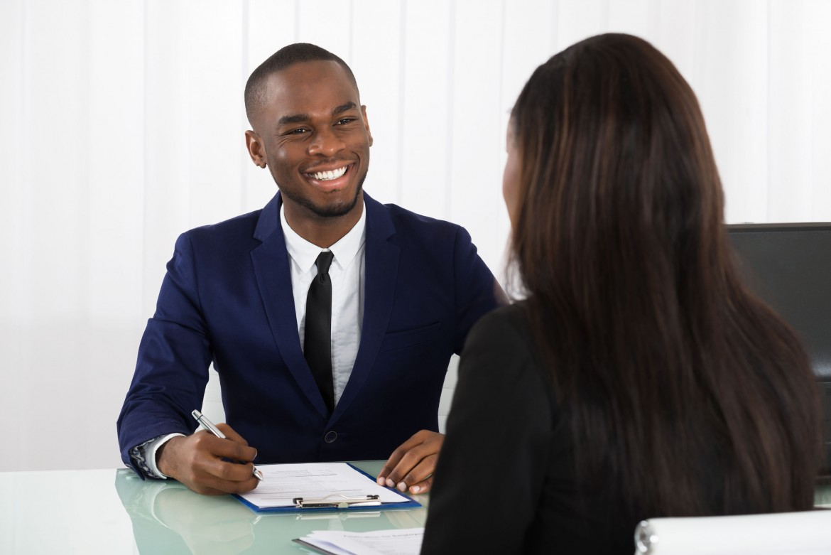 Male Human Resources Manager Interviewing A Young Female Applicant In Office
